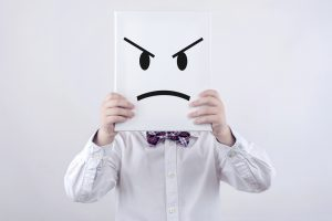 boy with bow tie holding angry face sign