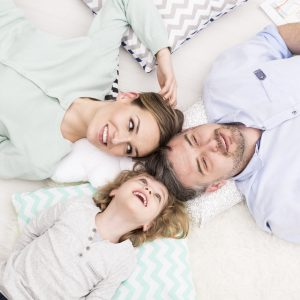 parents and daughter laying with heads together