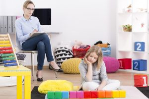 girl playing with blocks and psychologist taking notes